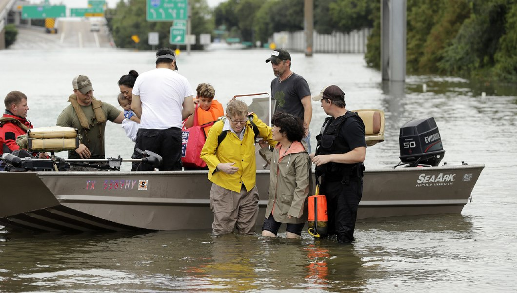 Residents are helped from a boat after being rescued from their flooded homes from Tropical Storm